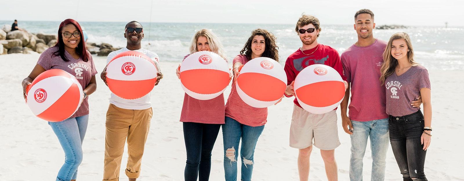 Students at beach holding Coastal beachballs